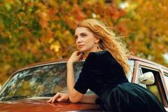 Schöne blonde Frau mit einem Retro- Auto im Herbst Stockbilder