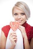 Schöne blonde Frau mit einem Valentinsgrußlutscher Stockbilder