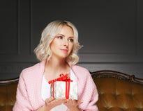 Schöne blonde Frau mit einem Weihnachtsgeschenk Lizenzfreies Stockfoto