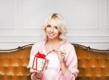 Schöne blonde Frau mit einem Weihnachtsgeschenk Lizenzfreies Stockbild