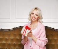 Schöne blonde Frau mit einem Weihnachtsgeschenk Lizenzfreie Stockbilder