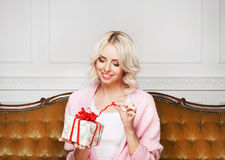 Schöne blonde Frau mit einem Weihnachtsgeschenk Lizenzfreie Stockfotografie