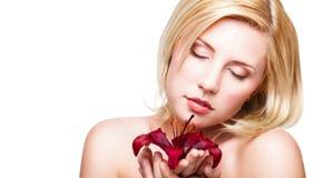 Schöne blonde Frau mit einer Blume Stockfoto