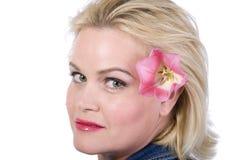 Schöne blonde Frau mit einer Blume in ihrem Haar Lizenzfreies Stockbild