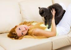Schöne blonde Frau mit einer Katze auf dem sofe Stockfotografie