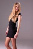 Schöne blonde Frau mit elegantem schwarzem Kleid lizenzfreie stockfotografie