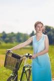Schöne blonde Frau mit Fahrrad draußen Lizenzfreie Stockbilder