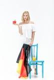 Schöne blonde Frau mit Flagge von Deutschland und von Gemüse Export und Import des Gemüses Stockbild