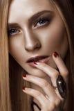 Schöne blonde Frau mit gesunden Haut und dem Haar, rote Maniküre, werfend im Studio auf Schönes lächelndes Mädchen Lizenzfreie Stockbilder