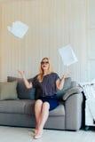 Schöne blonde Frau mit Gläsern sitzt auf der Couch und wirft oben Papier Stockbilder