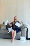 Schöne blonde Frau mit Gläsern sitzt auf der Couch und wirft oben Papier Lizenzfreie Stockbilder