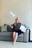 Schöne blonde Frau mit Gläsern sitzt auf der Couch und wirft oben Papier Stockfoto