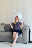 Schöne blonde Frau mit Gläsern sitzt auf der Couch und wirft oben Papier Lizenzfreie Stockfotos