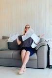 Schöne blonde Frau mit Gläsern sitzt auf der Couch und wirft oben Papier Lizenzfreie Stockfotografie