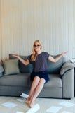 Schöne blonde Frau mit Gläsern sitzt auf der Couch und wirft oben Papier Lizenzfreies Stockbild