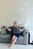 Schöne blonde Frau mit Gläsern sitzt auf der Couch und wirft oben Papier Stockfotografie