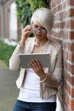 Schöne blonde Frau mit Gläsern und Tablette Stockfotos