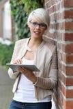 Schöne blonde Frau mit Gläsern und Tablette Lizenzfreie Stockbilder