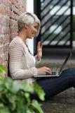 Schöne blonde Frau mit Gläsern und Tablette Lizenzfreie Stockfotografie