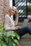 Schöne blonde Frau mit Gläsern und Tablette Stockbild