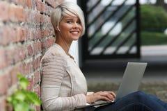 Schöne blonde Frau mit Gläsern und Tablette Stockbilder