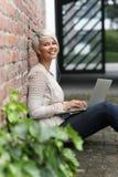 Schöne blonde Frau mit Gläsern und Tablette Stockfotografie