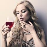Schöne blonde Frau mit Glasrotwein Stockfotos