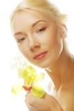 Schöne blonde Frau mit grüner Orchideenblume Stockfoto