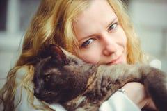 Schöne blonde Frau mit großer Katze draußen hält auf Schulter und lächelt Stockfotografie