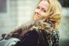 Schöne blonde Frau mit großer Katze draußen hält auf Schulter und lächelt Lizenzfreie Stockbilder