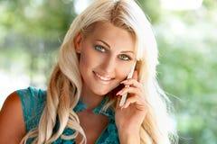 Schöne blonde Frau mit Handy Stockbild