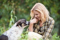 Schöne blonde Frau mit Hund im grünen Garten Lizenzfreies Stockbild