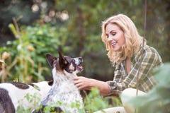 Schöne blonde Frau mit Hund im grünen Garten Stockbild