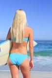 Schöne blonde Frau mit ihrem Surfbrett Stockfotografie