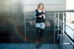 Schöne blonde Frau mit intelligentem Telefon nach Turnhallentraining Stockfotos
