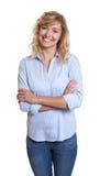 Schöne blonde Frau mit Jeans und den gekreuzten Armen Lizenzfreie Stockbilder