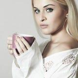 Schöne blonde Frau mit Kaffee. Tasse Tee Lizenzfreie Stockfotos