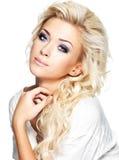 Schöne blonde Frau mit langem gelocktes Haar- und Artmake-up Lizenzfreie Stockfotografie