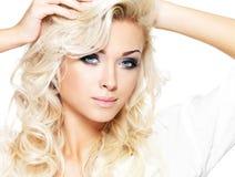 Schöne blonde Frau mit langem gelocktes Haar- und Artmake-up Stockbilder