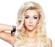 Schöne blonde Frau mit langem gelocktes Haar- und Artmake-up Lizenzfreies Stockbild