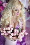 Schöne blonde Frau mit langer gewellter Frisur im purpurroten Dr. Lizenzfreies Stockbild