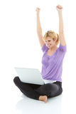 Schöne blonde Frau mit Laptop etwas online gewinnend Stockbild