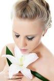 Schöne blonde Frau mit Lilienblume Stockbild