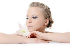 Schöne blonde Frau mit Lilienblume Stockfotografie