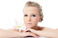 Schöne blonde Frau mit Lilienblume Lizenzfreie Stockfotografie