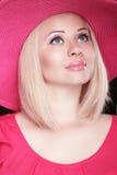 Schöne blonde Frau mit Make-up, lächelndes Mädchen, das in rosa h aufwirft Lizenzfreie Stockfotos