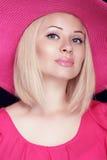 Schöne blonde Frau mit Make-up, lächelndes Mädchen, das in rosa h aufwirft Lizenzfreies Stockfoto