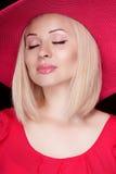 Schöne blonde Frau mit Make-up, sinnliches Mädchen, das in rotem ha aufwirft Stockfoto