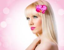 Schöne blonde Frau mit Orchideenblume Lizenzfreie Stockbilder