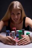 Schöne blonde Frau mit Pokerchips im Kasino Stockfoto